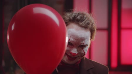 diabeł : A scary clown with cracked paint on the face peeking out from the red balloon and creepy smiling - evil clown concept