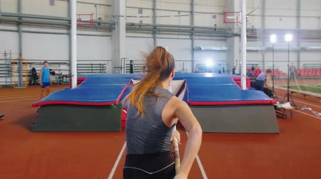pólus : Pole vaulting indoors - a young woman jumping over a bar with a pole