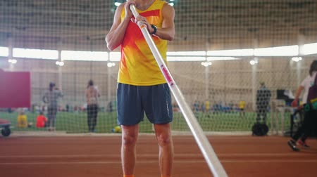 altura : Pole vaulting indoors - a man in yellow shirt standing on the track with a pole - sports stadium