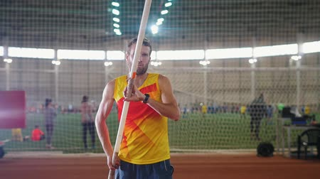 pólus : Pole vaulting indoors - a man in yellow shirt standing on the track with a pole - take deep breaths and starts running Stock mozgókép