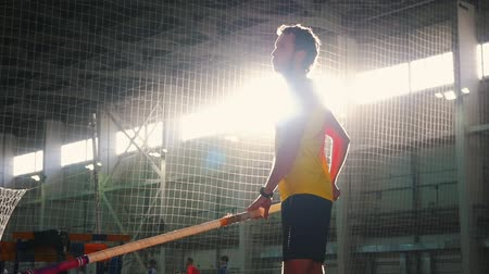 pólus : Pole vaulting indoors - a man in yellow shirt standing on the track with a pole and preparing for taking on on the jump Stock mozgókép