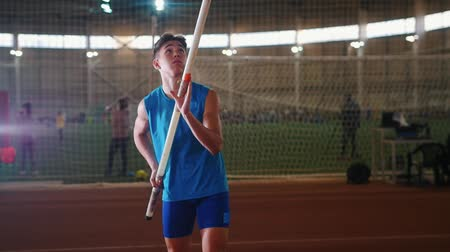pólus : Pole vaulting indoors - a young man in blue shirt standing on the track with a pole and preparing for taking on on the jump Stock mozgókép
