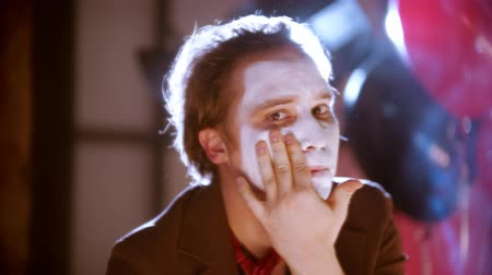 uğursuz : A man smearing white paint on his face in front of the mirror in the dressing room