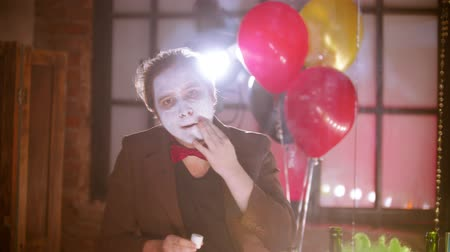 peruka : A man smearing white paint on his face in front of the mirror in the dressing room - balloons on the background