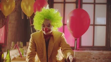peruka : A smiling creepy clown in the colorful costume hands the ball to the viewer and smile Wideo