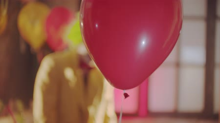 este : A red balloon passing by - a creepy clown on the background