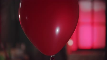 uğursuz : A red balloon passing by - a creepy clown turning around holding a balloon with a scary smile Stok Video