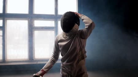 hekje : A young woman fencer putting on a protective helmet and gets into position Stockvideo