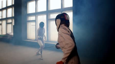 フェンシング : Two young women fencers having a training duel in the smoky studio