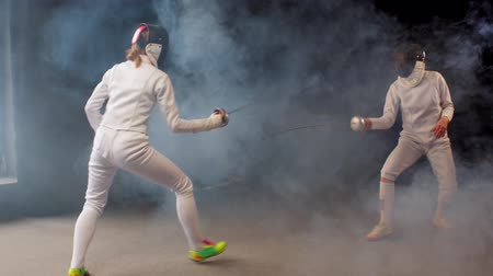 rivalidade : Two young women fencers having a dynamic training duel in the studio