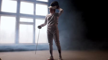 rivalidade : A young woman fencer putting on a protective helmet and gets into position - smoky studio