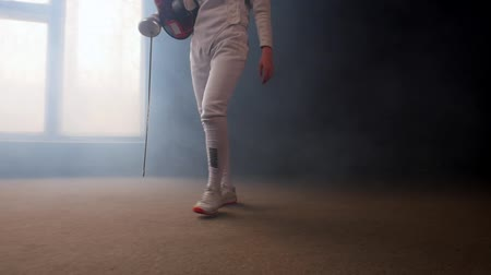 saber : A young woman fencer walking to the fighting area - smoky studio
