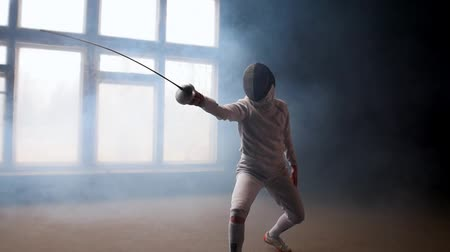 囲い : A young woman fencer showing basic attack movements on the fencing 動画素材