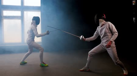 saber : Two young women fencers having a training duel in the studio