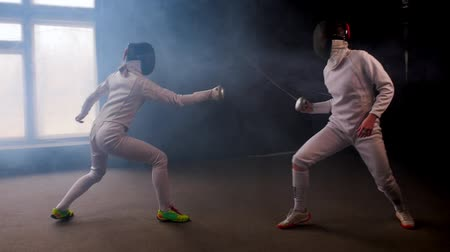 rivalidade : Two young women fencers having a dynamic training duel in the smoky studio