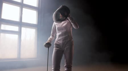 posição : A young pretty woman fencer putting on a protective helmet and gets into position