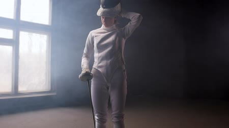 saber : A young woman fencer putting on a protective helmet and gets into position for the fight