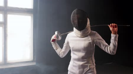 saber : A young woman fencer with a helmet putting the sword behind her shoulders in the studio Stock Footage