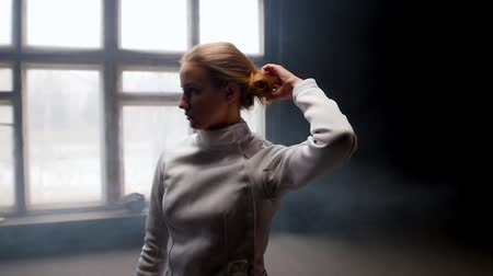 hekje : A young woman fencer she lets her hair down from the bun