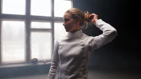 ona : A young woman fencer she lets her hair down and shakes her head