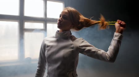 szermierka : A young woman fencer she lets her hair down and shakes her head down and back Wideo