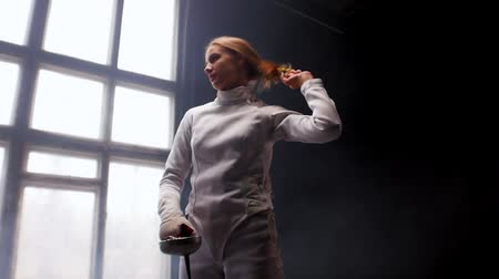 saber : A young woman fencer standing in the studio - lets her hair down from the bun