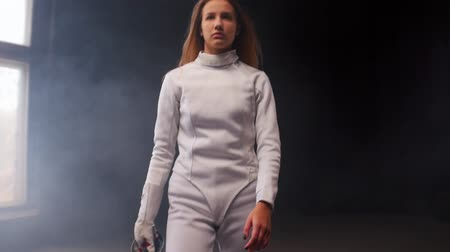 rivalidade : A young woman fencer putting the sword behind her shoulders in the studio Stock Footage