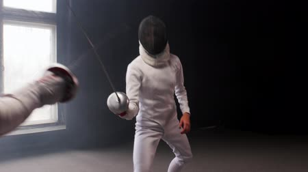 フェンシング : A young woman fencer walking to the fighting area and starts the duel