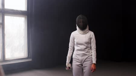 rivalidade : A young woman fencer walking to the fighting area and starts the training duel