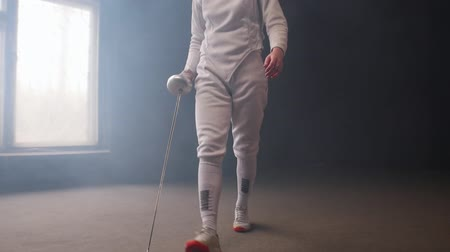 hekje : A young woman fencer with loose hair in white costume performing basic attack movements