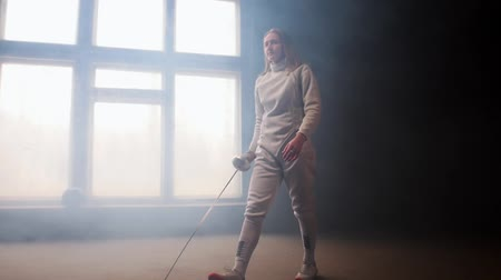 rivalidade : A young woman fencer walking to the fighting area with loose hair in white costume performing basic attack movements Stock Footage