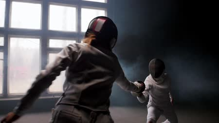szermierka : Two young women having a fencing duel in the smoky studio Wideo