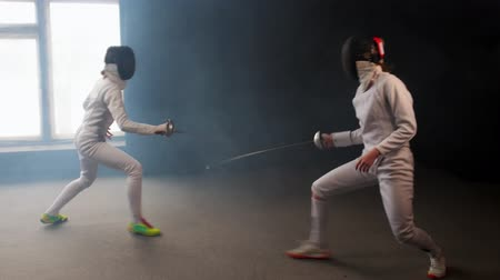 rivalidade : Two young women having an intense training in a fencing duel in the smoky studio Stock Footage