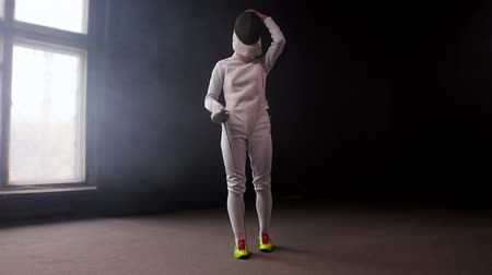 rivalidade : A young woman fencer walking to the fighting area and stands in the position
