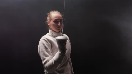 saber : A young woman fencer in the dark smoky studio