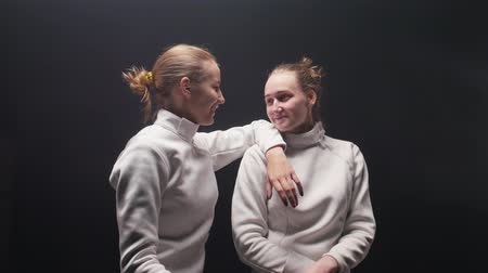 protective suit : Two young women fencers in white protective suits talking to each other - leaning on the shoulder of the friend