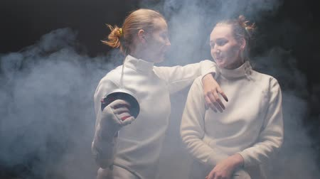rivalidade : Two young women fencers in white protective suits talking to each other - leaning on the shoulder of the friend and holding a sword