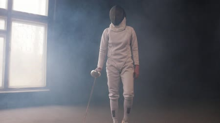 szermierka : A young woman fencer in white protective suit walking to the fighting area and starts the duel Wideo