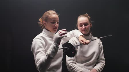 rivalidade : Two young women fencers fooling around with a sword when posing for the camera Stock Footage