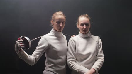 囲い : Two young women fencers standing in the dark studio - posing for the camera