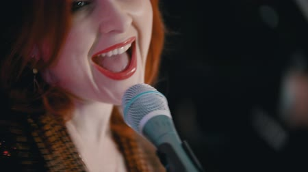 cantar : A musical band playing a cover song - ginger woman with red lipstick singing with a passion