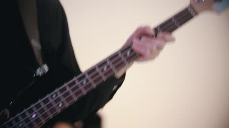 вести : A musical band playing a song in the white studio - a man playing bass guitar