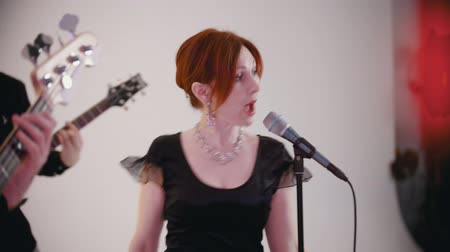 cantar : A musical band playing a song in the studio - adult ginger woman singing