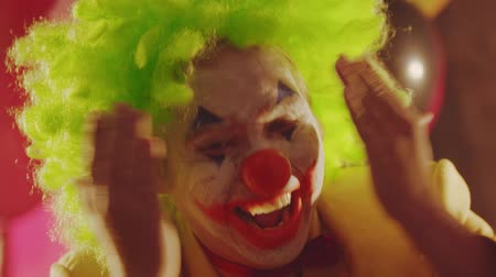 diabeł : A crazy smiling clown closing his face with his hands and performing creepy emotions