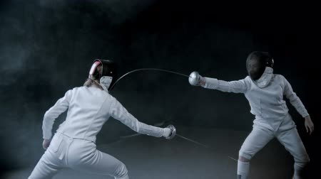 rivalidade : Fencing training - two women having a duel in the dark studio