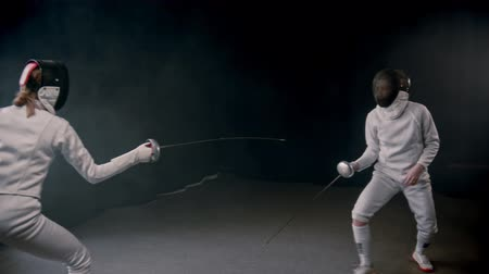 rivalidade : Fencing training - two women having a duel in protection costumes in the studio