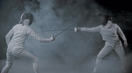 соперничество : Fencing training - two women having a duel in the smoky studio