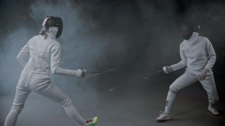 rivalidade : Fencing training - two young women having a duel in the smoky studio Stock Footage