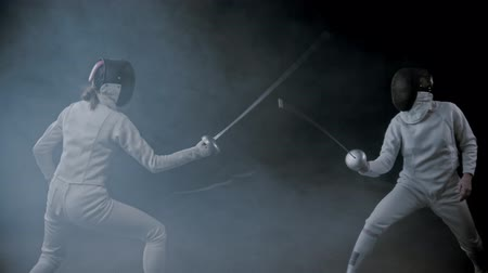囲い : Fencing training - two young women having a duel in the smoky studio - poking in each other 動画素材