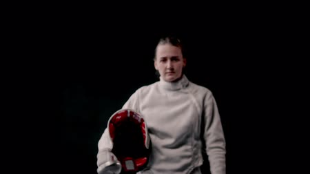 saber : Fencing training - young woman walking out from the dark and putting on a protective helmet - gets into position